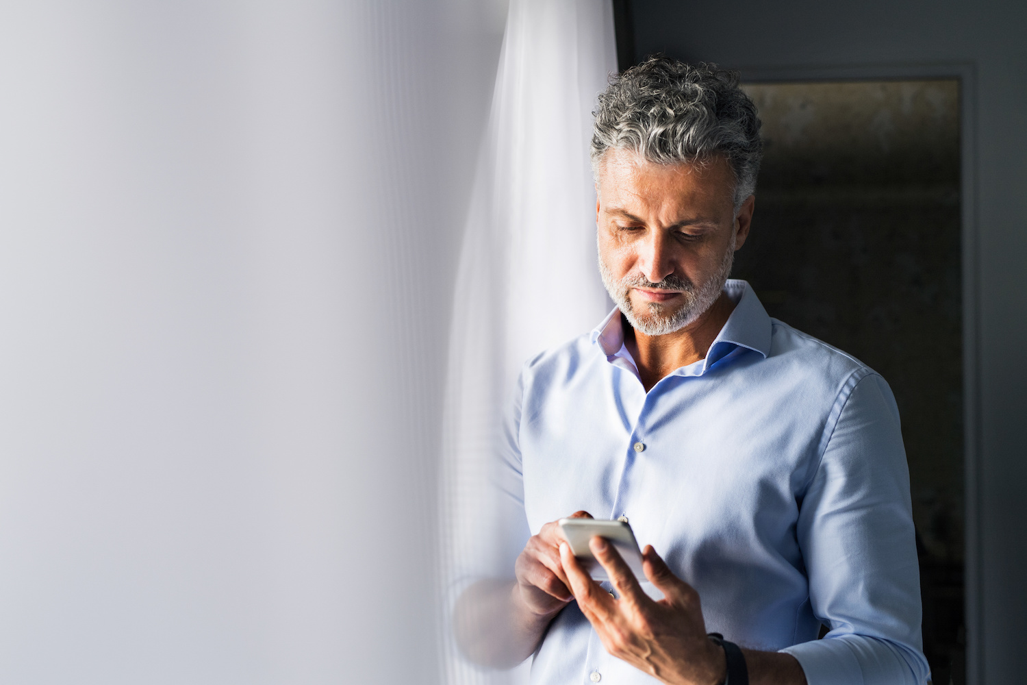 Mature businessman with smartphone in a hotel room. Handsome man standing at the window, texting. Close up.